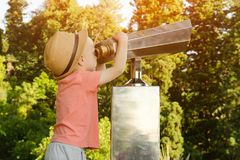 Kleiner blonder Junge im Hut, der in einem großen Paar Ferngläsern schaut Park im Hintergrund Stockfoto