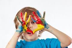 Kleiner blonder Junge mit den gemalten Händen auf weißem Hintergrund Stockfotos