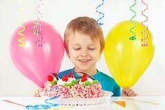 Kleiner blonder Junge mit einem Geburtstagskuchen und -ballonen Stockbild