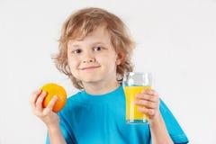Kleiner blonder Junge mit einem Glas des frischen Safts und der Orange Stockfotografie