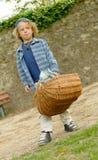 Kleiner blonder Junge mit einem Korb, draußen Stockbild