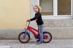 Kleiner blonder Junge mit einem roten Fahrrad Stockfoto