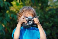 Kleiner blonder Junge mit einer Kamera schießt Sie Lizenzfreie Stockbilder