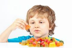 Kleiner blonder Junge mit Geleesüßigkeiten auf weißem Hintergrund Stockfotografie