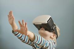 Kleiner blonder Junge mit Gläsern virtueller Realität Betrachtet das h Lizenzfreies Stockfoto