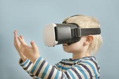 Kleiner blonder Junge mit Gläsern virtueller Realität Betrachtet das h Lizenzfreie Stockbilder