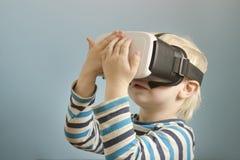 Kleiner blonder Junge mit Gläsern virtueller Realität Betrachtet das h Lizenzfreie Stockfotos