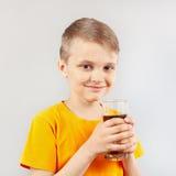 Kleiner blonder Junge mit Glas frischem Kolabaum Lizenzfreie Stockfotos