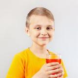 Kleiner blonder Junge mit Glas frischer roter Limonade Stockfotos