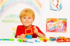 Kleiner blonder Junge mit Metallsäge im Klassenzimmer Lizenzfreies Stockfoto