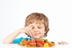 Kleiner blonder Junge mit Süßigkeiten auf weißem Hintergrund Lizenzfreie Stockfotografie