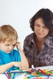 Kleiner blonder Junge mit seiner Mutter zeichnet mit Farbbleistiften Lizenzfreie Stockbilder