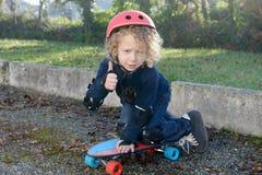 Kleiner blonder Junge mit Skateboard Stockfotos
