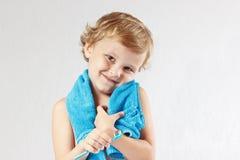 Kleiner blonder Junge mit Zahnbürste mit Zahnpasta Stockfotos
