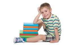 Kleiner blonder Junge nahe dem Stapel von Büchern Stockbilder