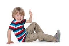 Kleiner blonder Junge sitzt auf dem Boden Stockbild