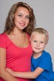 Kleiner blonder Junge umarmt seine Mutter Stockfotos
