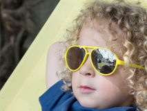 Kleiner blonder Junge und gelbe Sonnenbrille Lizenzfreie Stockfotografie