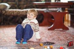 Kleiner blonder Junge von drei Jahren, die zu Hause mit Spielwaren spielen Lizenzfreie Stockbilder