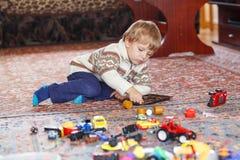 Kleiner blonder Junge von drei Jahren, die zu Hause mit Spielwaren spielen Lizenzfreies Stockbild
