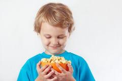 Kleiner blonder Junge, welche einer Schüssel nach Popcorn sucht Lizenzfreie Stockbilder