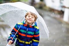 Kleiner blonder Kinderjunge auf Schulweg gehend während des Schneeregens, des Regens und des Schnees mit einem Regenschirm am kal Stockbild