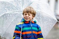 Kleiner blonder Kinderjunge auf Schulweg gehend während des Schneeregens, des Regens und des Schnees mit einem Regenschirm am kal Lizenzfreie Stockfotografie
