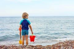 Kleiner blonder Kinderjunge, der auf einsamem Ozeanstrand steht Stockfotografie