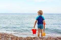 Kleiner blonder Kinderjunge, der auf einsamem Ozeanstrand steht Lizenzfreies Stockfoto