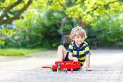 Kleiner blonder Kinderjunge in der bunten Kleidung, die mit rotem hölzernem spielt Stockfotos