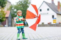 Kleiner blonder Kinderjunge, der draußen mit großem Regenschirm geht Lizenzfreie Stockfotografie