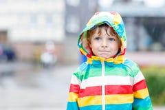 Kleiner blonder Kinderjunge, der draußen mit großem Regenschirm geht Lizenzfreie Stockbilder
