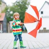 Kleiner blonder Kinderjunge, der draußen mit großem Regenschirm geht Stockbild