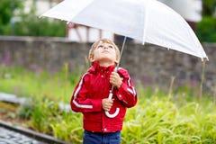 Kleiner blonder Kinderjunge, der draußen mit großem Regenschirm geht Stockfoto