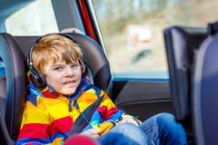 Kleiner blonder Kinderjunge, der Fernsehen oder dvd mit Kopfhörern während des langen Auto-Antriebs aufpasst Stockfotos