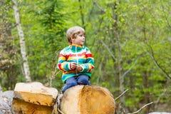 Kleiner blonder Kinderjunge, der im Wald am kalten Tag spielt Stockfotos