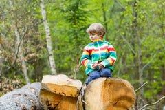 Kleiner blonder Kinderjunge, der im Wald am kalten Tag spielt Stockbilder