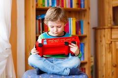 Kleiner blonder Kinderjunge, der mit hölzernem Spielzeugbus, zuhause spielt Lizenzfreie Stockbilder