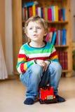 Kleiner blonder Kinderjunge, der mit hölzernem Spielzeugbus, zuhause spielt Stockbild