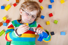 Kleiner blonder Kinderjunge, der mit vielen bunten Plastikblockes spielt Stockbild