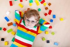 Kleiner blonder Kinderjunge, der mit vielen bunten Plastikblockes spielt Stockfotos
