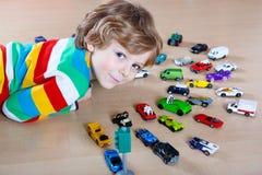 Kleiner blonder Kinderjunge, der mit vielen Spielzeugautos Innen spielt Stockbild