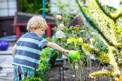 Kleiner blonder Kinderjunge, der mit Wasserkanisterspielzeug spielt Lizenzfreies Stockbild