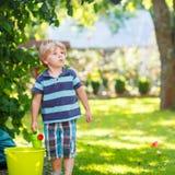 Kleiner blonder Kinderjunge, der mit Wasserkanisterspielzeug spielt Stockfotografie