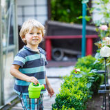 Kleiner blonder Kinderjunge, der mit Wasserkanisterspielzeug spielt Stockfotos