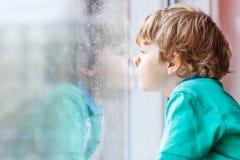Kleiner blonder Kinderjunge, der nahe Fenster sitzt und auf Regentropfen schaut Stockfoto