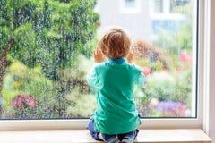 Kleiner blonder Kinderjunge, der nahe Fenster sitzt und auf Regentropfen schaut Stockbild