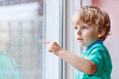 Kleiner blonder Kinderjunge, der nahe Fenster sitzt und auf Regentropfen schaut Stockfotos