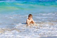 Kleiner blonder Kinderjunge, der Spaß auf Ozeanstrand in Florida hat Stockbild