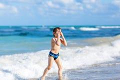 Kleiner blonder Kinderjunge, der Spaß auf Ozeanstrand in Florida hat Stockbilder